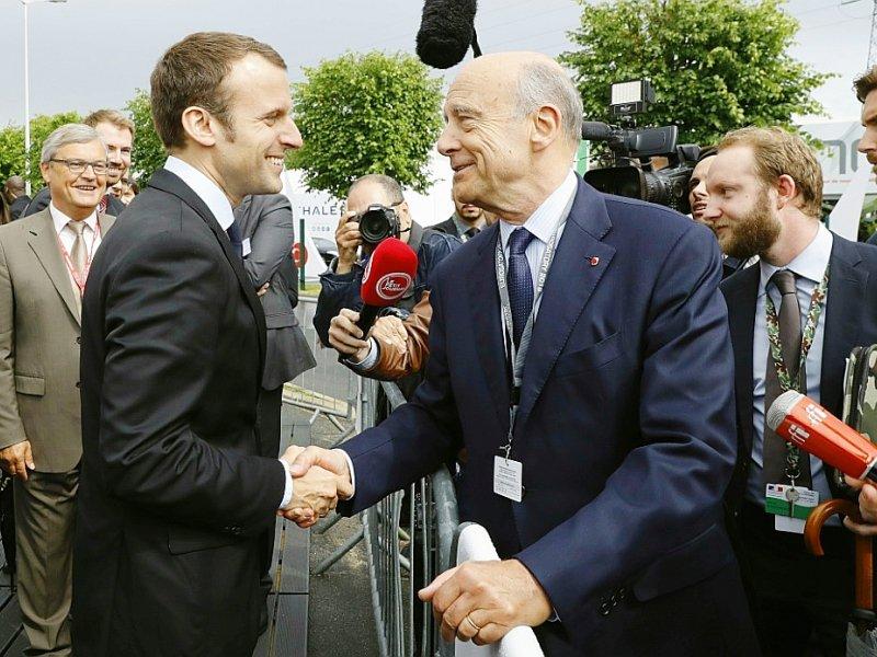 Emmanuel Macron et Alain Juppé se saluent lors du salon Eurosatory, le 16 juin 2016 à Villepinte (Seine-Saint-Denis) - PATRICK KOVARIK [AFP/Archives]