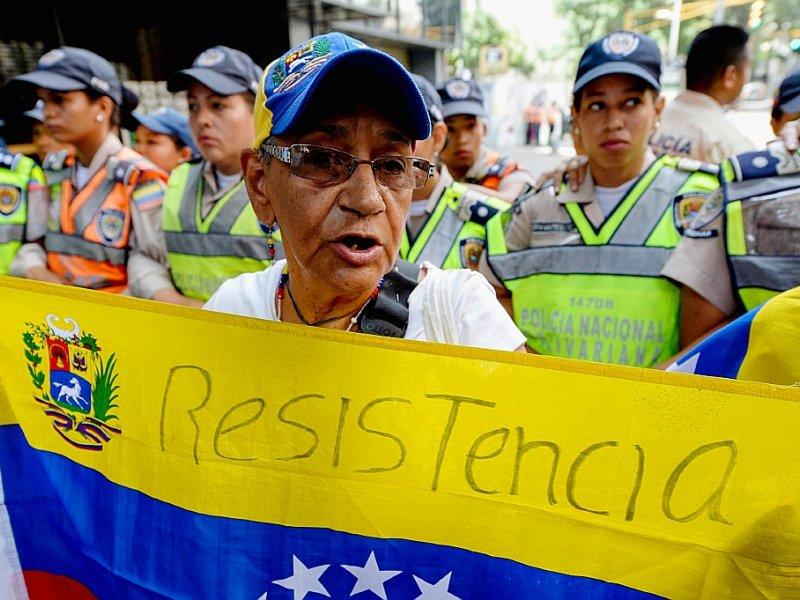 Un membre de l'opposition au président Nicolas Maduro porte un drapeau lors d'une manifestation à Caracas le 10 novembre 2016 - FEDERICO PARRA [AFP]