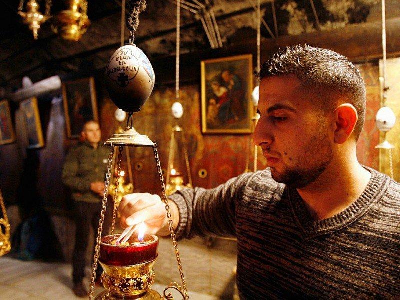 Un homme allume de l'encens dans l'Eglise de la Nativité, où Jésus-Christ est né selon la Bible, à Béthléem en Cisjordanie - MUSA AL SHAER [AFP]