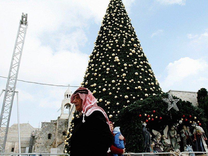 Un Palestinien le 20 décembre 2016 près d'un sapin de Noël géant place de la Mangeoire, à côté de l'Eglise de la Nativité, à Béthléem, lieu de naissance du Christ selon la Bible - MUSA AL SHAER [AFP/Archives]