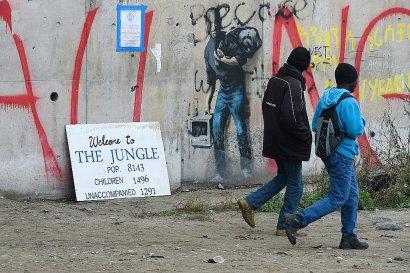 """Des réfugiés passent devant un graffiti de l'artiste de rue Banksy représentant en migrant le fondateur d'Apple, Steve Jobs, à l'époque de l'évacuation complète du camp de la """"Jungle"""" de Calais, à Calais, le 24 octobre 2016    DENIS CHARLET [AFP]"""