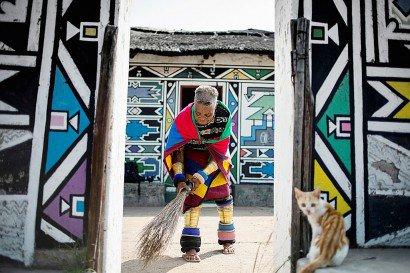 Dans sa jupe traditionnelle à perles, le cou et les jambes encerclés d'anneaux de cuivre, Esther Mahlangu balaie la cour devant sa hutte. - GULSHAN KHAN [AFP/Archives]