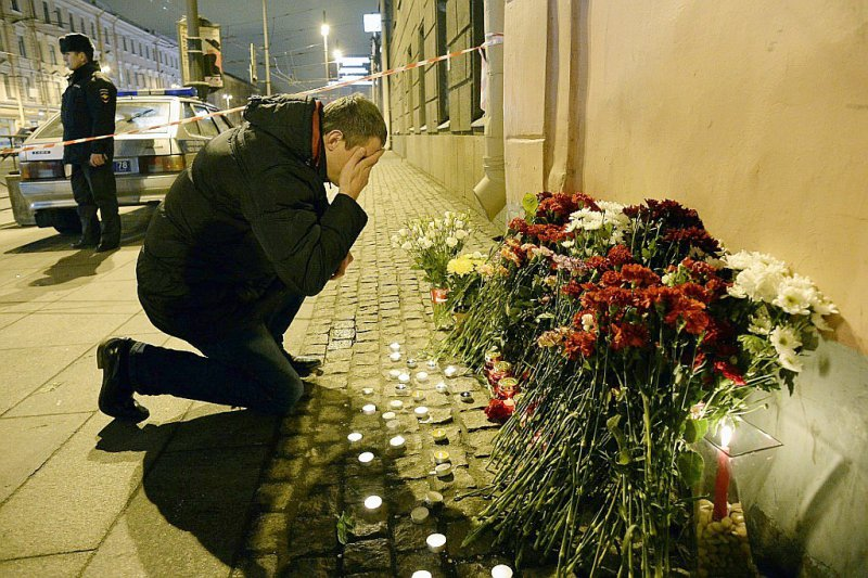 Un homme se recueille après avoir déposé des fleurs en mémoire aux victimes d'un attentat dans le métro, le 3 avril 2017 à Saint-Pétersbourg - Olga MALTSEVA [AFP]