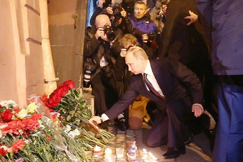 Le président russe Vladimir Poutine dépose des fleurs en hommage aux victimes de l'attentat dans le métro, le 3 avril 2017 à Saint-Pétersbourg - [AFP]