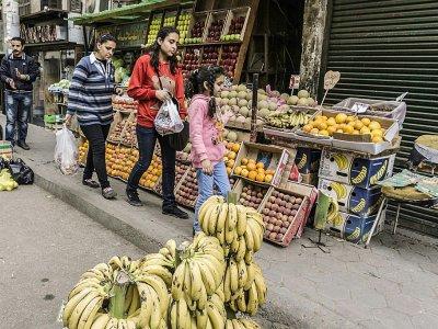 Des Egyptiennes passent devant un étal de fruits, dans une rue du quartier de la Choubra, le 11 avril 2017 au Caire - KHALED DESOUKI [AFP]