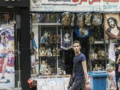 Un homme passe devant une boutique d'objets et de bibelots religieux, dans le quartier de la Choubra, le 11 avril 2017 au Caire, en Egypte - KHALED DESOUKI [AFP]