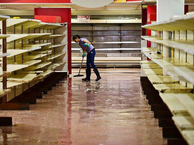 Un employé passe la serpillère dans un supermarché à Valencia au Venezuela, le 5 mai 2017 - RONALDO SCHEMIDT [AFP]