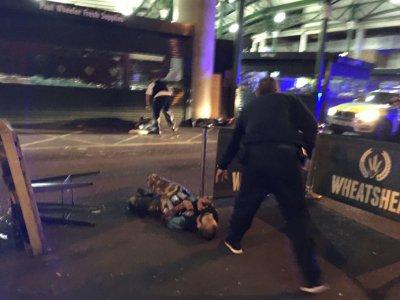 Un policier armé à côté de deux suspects à terre à Borough Market, dans le centre de Londres, le 3 juin 2017    Gabriele SCIOTTO [AFP]
