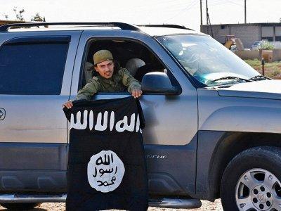 Un membre des forces syriennes pro-gouvernementales tient un drapeau du groupe Etat islamique après avoir repris à Daech le village de Dibsiafnan aux abords de Raqa, en Syrie, le 11 juin 2017 - George OURFALIAN [AFP]