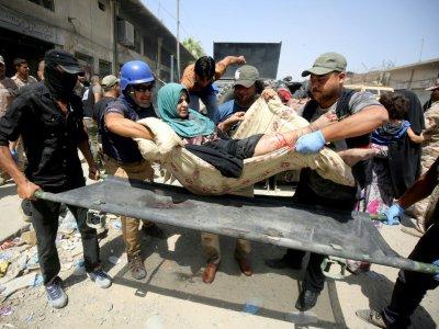 Des membres des forces de sécurité irakiennes transportent une femme blessée lorsqu'un kamikaze s'est fait exploser, le 23 juin 2017 à Mossoul - AHMAD AL-RUBAYE [AFP]