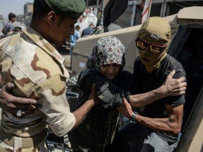 Une femme qui a fui les combats dans la Vieille ville de Mossoul, est prise en charge par les forces armées irakiennes, le 23 juin 2017 - MOHAMED EL-SHAHED [AFP]
