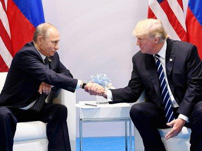 Donald Trump et Vladimir Poutine se serrent la main au cours d'une rencontre, la première, en marge du sommet du G20 à Hambourg, en Allemagne, le 7 juillet 2017.    SAUL LOEB [AFP]