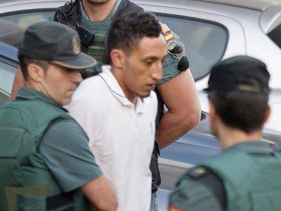 Driss Oukabir, un Marocain de 27 ans, membre présumé de la cellule jihadiste responsable des attentats en Catalogne, sort d'un centre de détention escorté par la guarde civile le 22 août 2017 à Tres Cantos, près de Madrid    STRINGER [AFP]