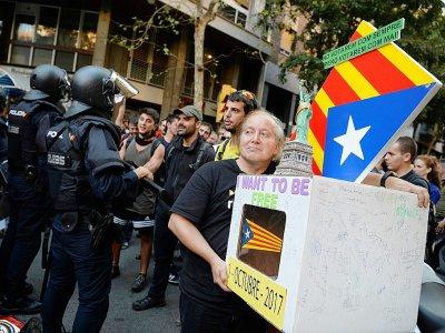 Une personne porte une urne symbolique face à des policiers espagnols en soutien au référendum catalan. Le 20 septembre 2017.    Josep LAGO [AFP]