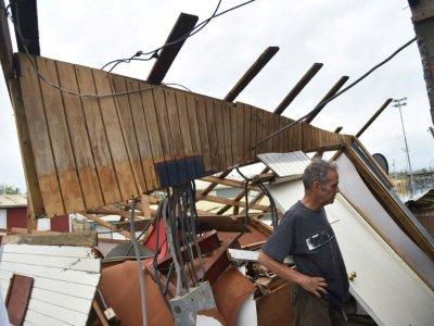 Un homme examine les restes de sa maison à Catano, à Porto Rico, le 21 septembre 2017 après le passage de l'ouragan Maria - HECTOR RETAMAL [AFP]