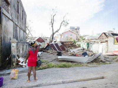 une femme observe les restes d'une maison à Roseau, capitale de la Dominique, le 21 septembre 2017 après le passage de l'ouragan Maria - Lionel CHAMOISEAU [AFP]