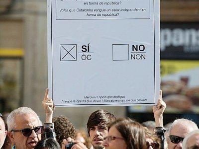 Un manifestant partisan du référendum sur l'indépendance catalane brandit un bulletin de vote géant à Barcelone le 16 septembre 2017 - Josep LAGO [AFP/Archives]