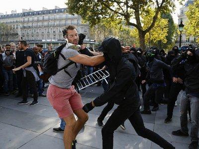 Un manifestant s'interpose face à un groupe de personnes cagoulées qui perturbent la manifestation de la France Insoumise contre les réformes du travail, Place de la République à Paris, le 23 septembre 2017 - Zakaria ABDELKAFI [AFP]
