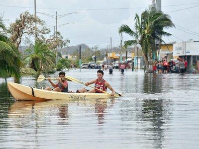 Des habitants utilisent un kayak pour se déplacer dans leur rue inondée, à Juana Matos, sur lîle de Porto Rico, le 21 septembre 2017 après le passage de l'ouragan Maria - HECTOR RETAMAL [AFP]