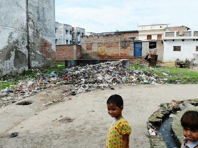 Des enfants dans les rues jonchées de détritus dans la ville de Gonda en Inde, le 20 août 2017 - SAJJAD HUSSAIN [AFP]