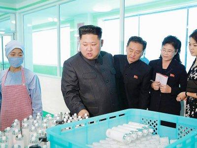 Photo du 29 octobre 2017 de l'agence de presse Nord coréenne (KCNA) montrant le leader nord-Coréen Kim Jong-Un (2eG) dans usine avec sa femme Ri Sol-Ju (D)    STR [KCNA VIA KNS/AFP]