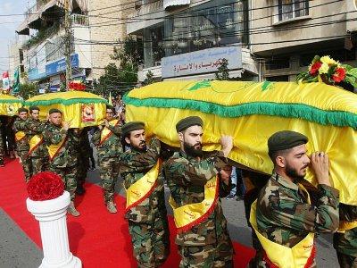 Des membres du Hezbollah portent les cercueils de trois de leurs camarades tués en Syrie en combattant au côté du régime, lors de funérailles à Nabatiyeh dans le sud du Liban le 8 novembre 2017    Mahmoud ZAYYAT [AFP]