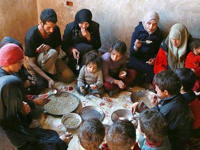 Une famille partage un maigre repas à base de choux et de maïs dans la Ghouta orientale assiégée près de Damas, le 6 novembre 2017    ABDULMONAM EASSA [AFP]
