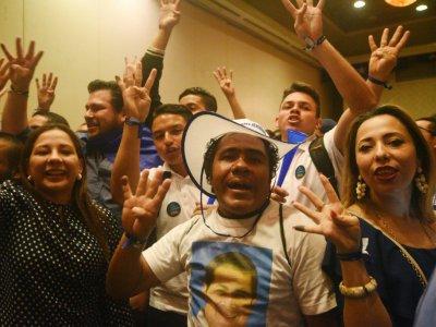 Des sympathisants du président hondurien sortant Juan Orlando Hernandez fêtent sa victoire, qu'il a annoncé lui-même dimanche avant les résultats officiels, et qui est contestée par son principal opposant à l'élection présidentielle.    RODRIGO ARANGUA [AFP]