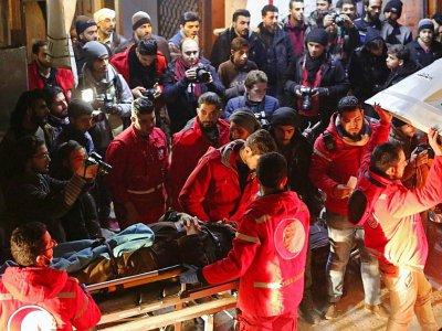 Des volontaires du Croissant-rouge syrien transportent un malade dans une ambulance pour l'évacuer de Douma vers Damas où il doit recevoir des soins, tard le 28 décembre 2017    Amer ALMOHIBANY [AFP]