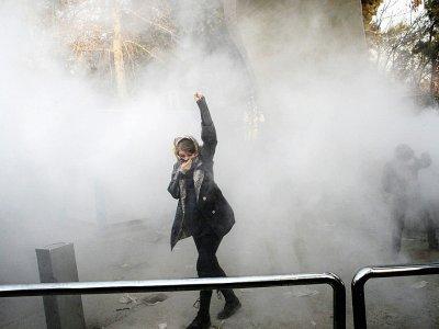 Une Iranienne dans la fumée de gaz lacrymogène lors de manifestations à l'université de Téhéran, le 30 décembre 2017    STR [AFP]