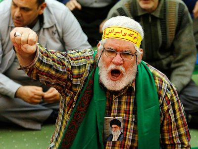 Un fidèle iranien avec un portrait du numéro un iranien Ali Khamenei accroché autour du cou prend part aux prières à la mosquée Imam Khomeiny à Théran, le 5 janvier 2018    ATTA KENARE [AFP]