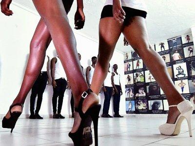 Des apprentis-mannequins apprennent à défiler lors d'un cours à l'agence de Fatim Sidimé, top model ivoirienne, le 20 décembre 2017 à Abidjan - SIA KAMBOU [AFP]