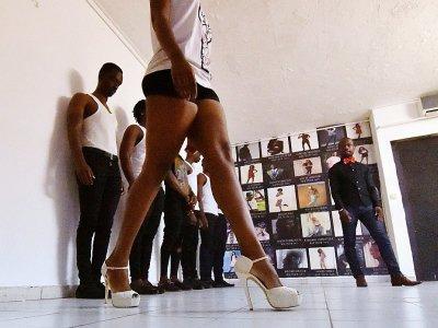 Le chorégraphe Franck Akesse (d) s'adresse à des apprentis-mannequins lors d'un cours de défilé de l'agence de Fatim Sidimé, top model ivoirienne, le 20 décembre 2017 à Abidjan - SIA KAMBOU [AFP]