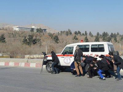 Des journalistes afghans se réfugient derrière une ambulance pendant les combats dans l'hôtel Intercontinental de Kaboul, le 21 janvier 2018    SHAH MARAI [AFP]
