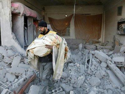 Un membre de la Defense civile porte le corps d'un enfant, retrouvé dans les décombres d'un bâtiment touché par des raids du régime dans la ville rebelle de Jisrine, à l'est de Damas le 8 février 2018 - ABDULMONAM EASSA [AFP]