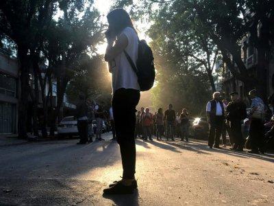 Une jeune femme au téléphone dans les rues de Mexico City après qu'un séisme évalué à une magnitude de 7.0 ait secoué la ville, le 16 février 2018 - PEDRO PARDO [AFP]