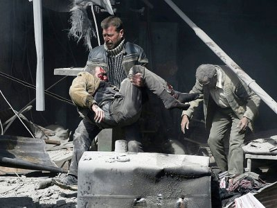 Un homme au secours d'un blessé après les bombardements du régime syrien contre la ville rebelle de Hammouriyé, le 19 février 2018    ABDULMONAM EASSA [AFP]
