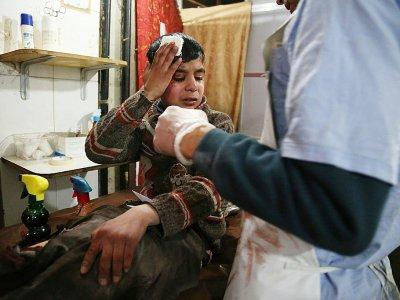 Ghaith, un adolescent de 12 ans, est soigné dans un hôpital de Kafr Batna et attend des nouvelles de sa mère opéré dans une salle voisine après le bombardement de leur ville dans la Ghouta orientale par le régime syrien le 19 février 2018    Ammar SULEIMAN [AFP]