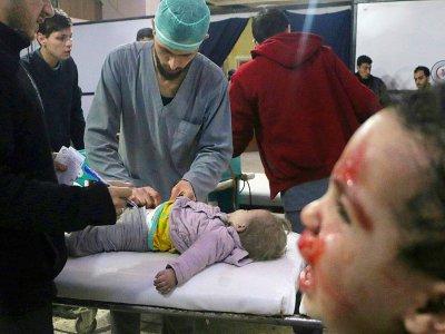 Des secouristes soignent un enfant blessé alors qu'un autre pleure dans une clinique de fortune à Douma, dans la Ghouta orientale, bombardée par le régime, le 22 février 2018    Hamza AL-AJWEH [AFP]