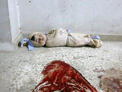 Le corps d'un enfant syrien enveloppé dans une couverture et placé à même le sol dans une clinique de fortune dans la localité de Douma, dans le fief rebelle de la Ghouta orientale, cible de bombardements intensifs du régime, le 22 février 2018    Hamza AL-AJWEH [AFP]