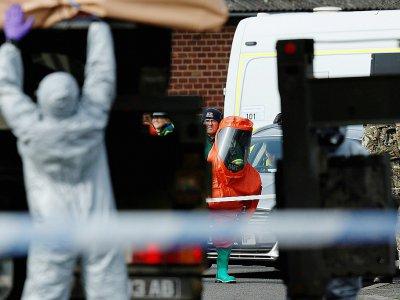 Les enquêteurs britanniques, en tenue de protection contre les risques chimiques procèdent à l'enlèvement d'un véhicule lié à l'enquête sur l'empoisonnement de Sergueï Skripal, le 14 mars 2018 à Gillingham, dans le sud-est de l'Angleterre.    Adrian DENNIS [AFP]