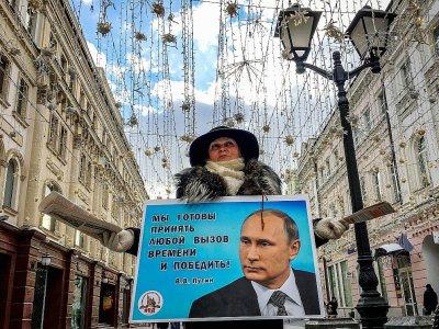 Une militante distribue des tracts en faveur de Vladimir Poutine dans une rue de Moscou, le 16 mars 2018    Yuri KADOBNOV [AFP]