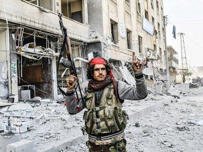 Un rebelle syrien allié aux forces turques paradent dans la ville kurde d'Afrine, dans le nord-ouest de la Syrie, le 18 mars 2018 - Bulent Kilic [AFP]