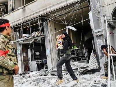 Des combattants syriens soutenus par l'armée turque pillent des magasins après la chute de la ville kurde syrienne d'Afrine le 18 mars 2018 - BULENT KILIC [AFP]