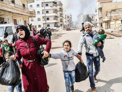 Des civils tentent de fuir les bruits d'explosion dans la ville kurde d'Afrine, dans le nord-ouest de la Syrie, le 18 mars 2018 - Bulent Kilic [AFP]