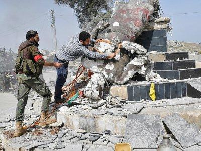 Des rebelles syriens pro-turcs déboulonnent une statue kurde dans le centre de la ville d'Afrine (nord-ouest de la Syrie), le 18 mars 2018 - Bulent Kilic [AFP]