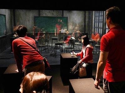 """Des visiteurs découvrent l'installation """"La Classe"""" lors de l'exposition consacrée à l'artiste argentin Leandro Erlich au Musée Mori de Tokyo, le 4 mars 2018    Toru YAMANAKA [AFP]"""