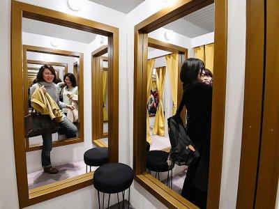 """Des visiteuses découvrent l'installation """"Cabine d'essayage"""" lors d'une exposition consacrée à l'artiste argentin Leandro Erlich, le 4 mars 2018 au musée Mori à Tokyo    Toru YAMANAKA [AFP]"""