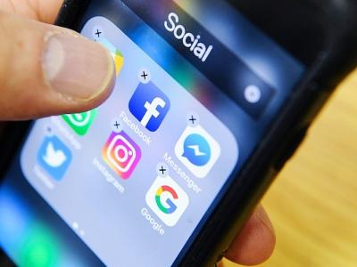 Un homme tient un smartphone sur lequel on voit des icones dont celui de l'application Facebook, à Moscou le 23 mars 2018 - Kirill KUDRYAVTSEV [AFP/Archives]