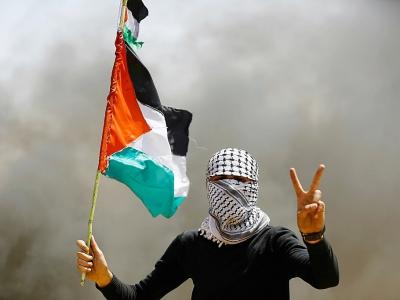 Un manifestant palestinien au visage recouvert par un keffieh lors d'une manifestation le 6 avril 2018 près de la frontière entre la bande de Gaza et Israël - MOHAMMED ABED [AFP]